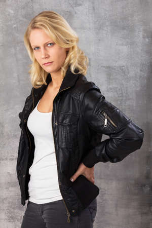 Serious modern blonde woman, with hands on hips looking at the camera  Studio shot against a gray background  Stock Photo