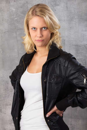 angry blonde: Portrait of a pouting young blonde woman, with hands on hips looking at the camera  Studio shot against a gray background Stock Photo