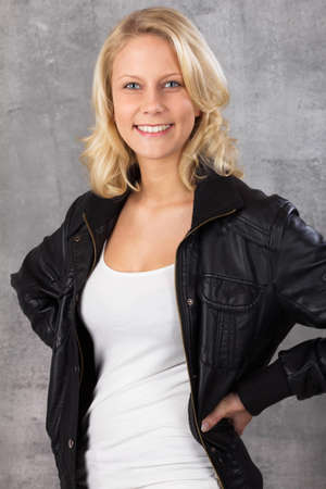 Happy smiling young blonde woman, with hands on hips looking at the camera  Studio shot against a gray background Stock Photo