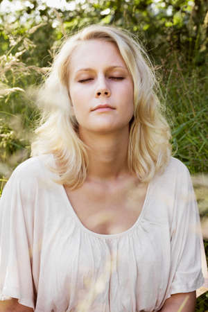 Portrait in profile of a daydreaming young Blond woman with closed eyes  Summer outdoor shot between a blurry green and sunny grass background  Stock Photo - 14002067