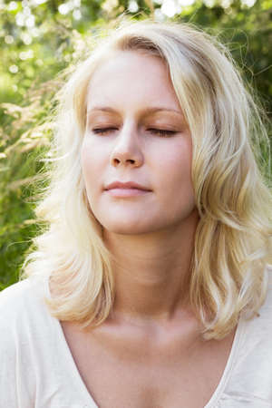 Portrait of a meditating blond woman with closed eyes  Summer outdoor shot against a blurry green background Stock Photo - 14002065