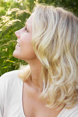 Portrait in profile of a happy young blonde woman with a smile looking to the side  Summer outdoor shot against a blurry green background  photo
