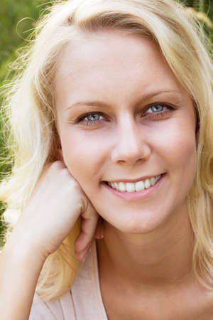 Portrait of a happy blonde woman with a smile looking at the camera  Summer outdoor shot against a blurry green background Stock Photo - 14002062
