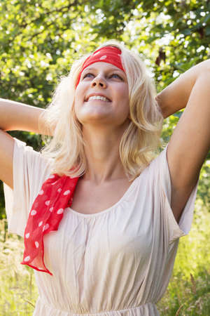 Happy young blonde woman with hands in the neck  Summer outdoor portrait against a blurry green background  Stock Photo - 14342620