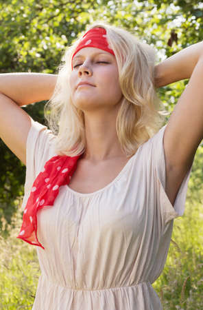 Daydreaming young blond woman with closed eyes and headband  Summer outdoor portrait against a blurry green background  photo