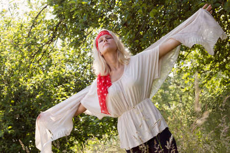 Young woman woman with with outstretched arms flying in the summer  Outdoor shot against a natural green background photo