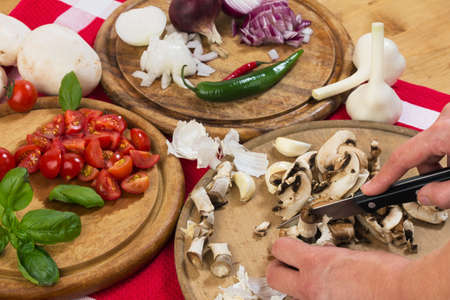 Slicing champignons and tomatoes with a knife on a wooden board, studio shot with hands for healthy food photo