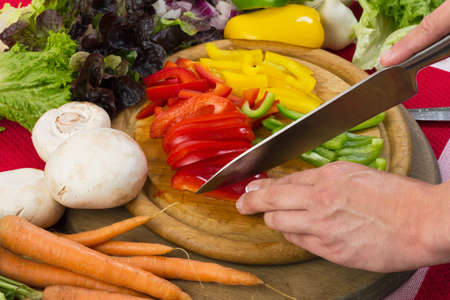 Cutting pepper and vegetables with a knife on a wooden board, studio shot with hands for healthy food photo