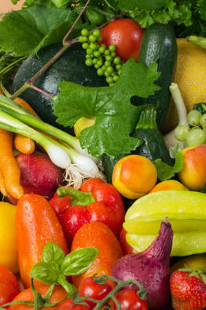 vertical wellness: Fresh fruit and vegetables like tomatoes, zucchini, melons, grapes and leaves wet arranged in a group, natural still life for healthy food Stock Photo
