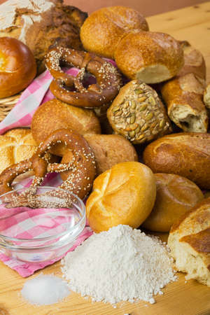 Baking bread -  rolls, pretzels, white bread, arranged in a group, food still life in warm colors with ingredients