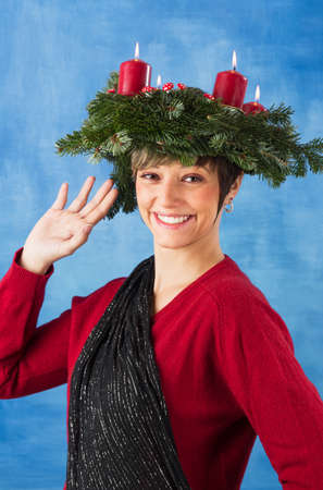 Waving young woman woman wearing advent wreath on her head, four candles are burning  Studio shot against a blue background, series