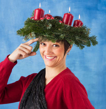 Smiling young woman woman wearing advent wreath on the head taps her forehead  Funny studio shot against a blue background, series photo