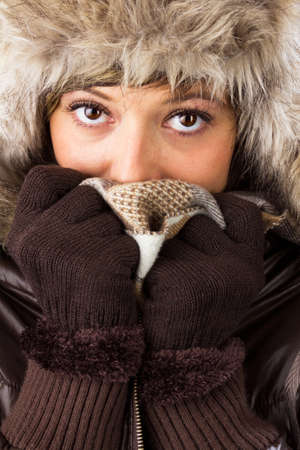 Beautiful young woman with big bright eyes in winter clothes covers her face to protect from the cold  Studio shot as a wintry close up portrait Stock Photo
