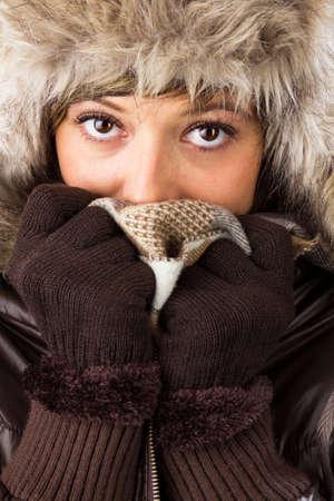 ropa de invierno: Joven y bella mujer con grandes ojos brillantes en la ropa de invierno se cubre la cara para protegerse del fr�o Studio dispar� como un cierre invernal Retrato