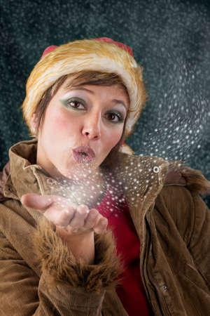 Bella femmina Babbo Natale come Natale fata soffia un bacio fatto di neve e stelle ritratto sensuale studio contro uno sfondo verde scuro photo