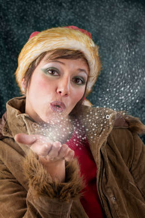 Pretty female Santa Claus as christmas fairy blowing a kiss out of snow and stars  Sensual Studio portrait against a dark green background photo