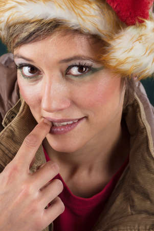 Seductive female Santa Claus as christmas fairy with a slight smile and big bright eyes  Sensual xmas studio portrait photo