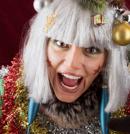 kitsch: Cry for christmas - excited screaming woman with open mouth like a decorated santa claus  Funny xmas studio shot against a red background Stock Photo