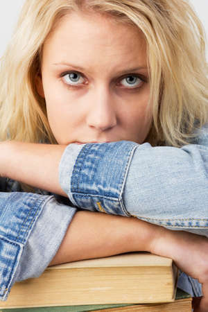 book jacket: Portrait of a young blonde woman, as female student looking frustrated and leaning on her books, studio shot against a white background Stock Photo