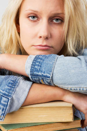 book jacket: Portrait of a young blonde woman, as female student looking tired and leaning on her books, studio shot against a white background Stock Photo