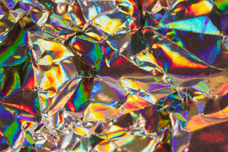 Detail close up of strongly wrinkled metallic paper as a colorful fantasy background image in rainbow colors with focus at the center Stock Photo - 21766086