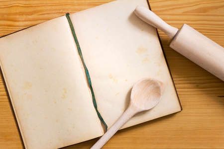 Opened yellowed cookbook with blank pages, cooking spoon and rolling pin on wooden background - bright cooking still life with copy space