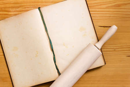 Opened yellowed cookbook with blank pages and rolling pin on wooden background - cooking still life with copy space