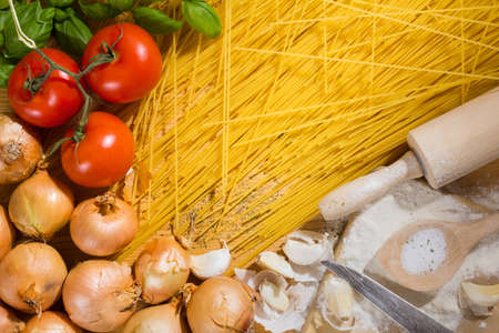 Italian pasta - cooking spoon, rolling pin, spaghetti and ingredients like, onions, tomatoes, garlic basil and flour and salt on wooden background
