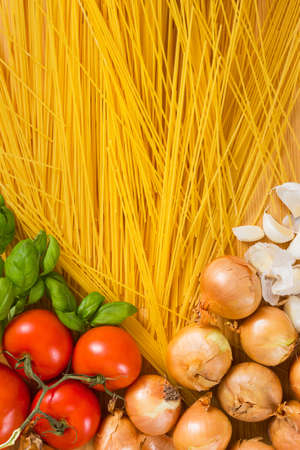 Italian pasta - spaghetti, vegetables and ingredients like, onions, tomatoes, garlic and basil on wooden background