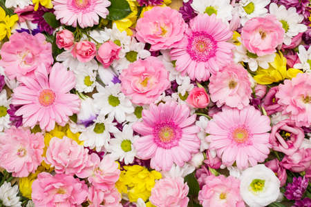 Roses, gerbera and other flowers arranged as a colorful natural background image with white, yellow and pink blossoms