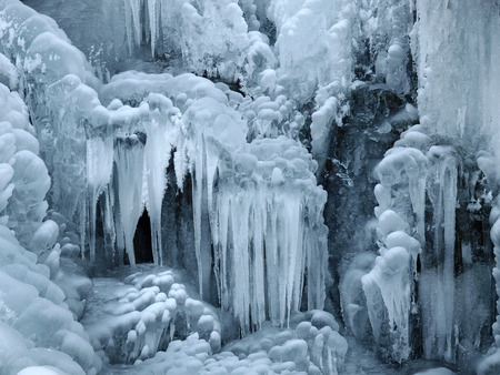 A frozen waterfall with ice in a blue and white color in winter 写真素材