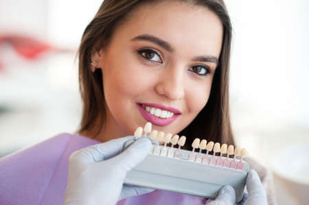 Dentist checking and selecting color of young womans teeth.