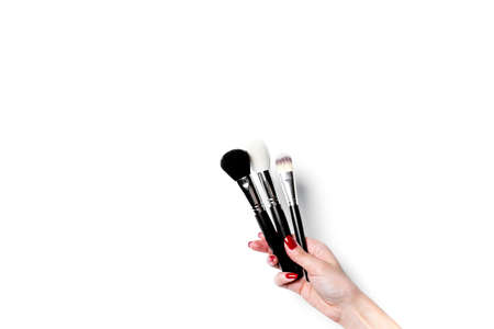 Professional make-up brush cosmetic in female hand beautician isolated on white background.