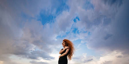 Redhead girl at spring blue sky background.