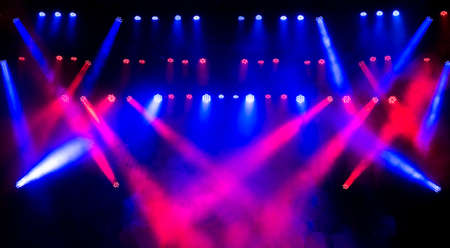 Beautiful concert light on an empty stage in the smoke. Disco and laser show.