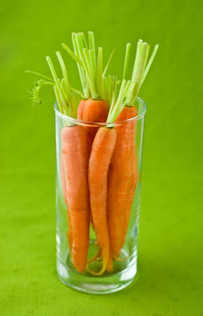 Fresh young carrots in glass ready to make carrot juice