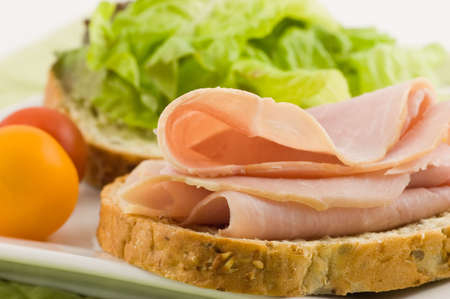 Open faced ham sandwich on whole grain bread with lettuce and cherry tomatoes makes a healthy lunch photo