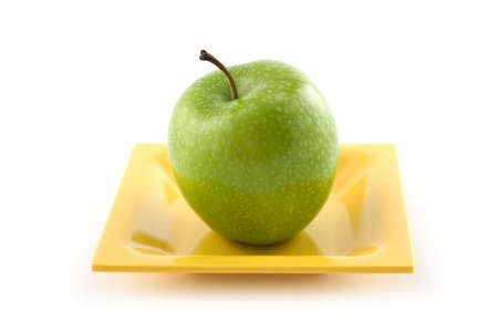 Granny Smith apple on yellow ceramic plate isolated on white background Stock Photo