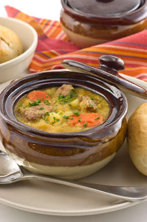 Hearty beef stew in glazed dish with bread roll
