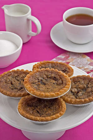Butter tarts and tea on deep pink tablecloth
