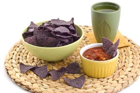 Blue corn tortilla chips with black bean and sweet corn salsa on braided grass mat