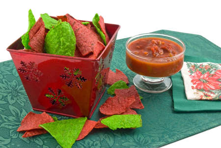 Red and green tortilla chips in christmas theme container with black bean and corn salsa on green mat