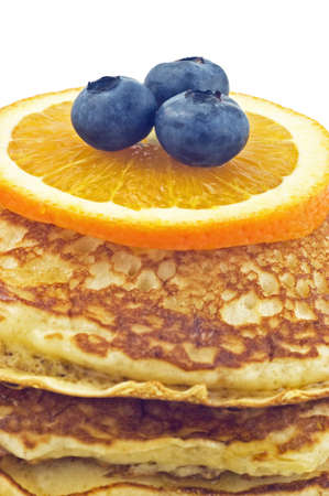 Buttermilk pancakes with blueberries and orange slice isolated on white background