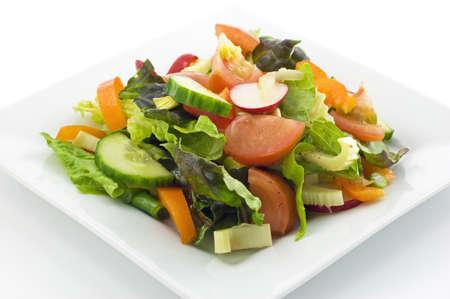 Garden salad with balsamic vinaigrette dressing isolated on white background