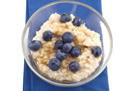 Oatmeal with blueberries and brown sugar in glass bowl on blue napkin Stock Photo