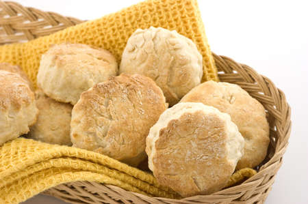 Freshly baked golden scones, or baking powder biscuits in wicker basket