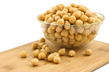 Washed and drained canned chick peas in glass dish on bamboo board isolated on white background 版權商用圖片 - 9248480
