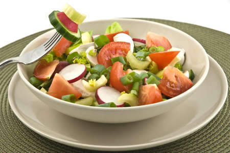 Small bowl of salad with fresh greens, tomatoes, radishes, cucumber, mushrooms isolated on white background