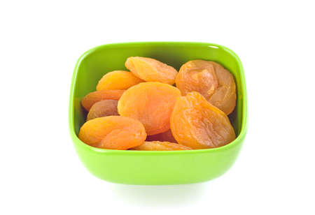 Dried apricots in green dish isolated on white background with copy space