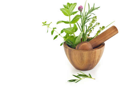 Wooden mortar and pestle with herbs, isolated on white background with copy space, in horizonal format Stock Photo